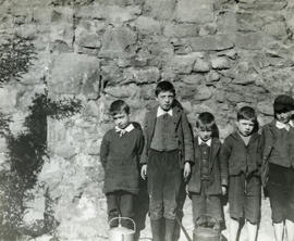 Group of five boys leaning against retaining stone wall in backcourt garden