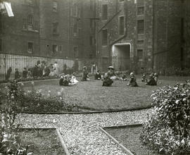 Children seated in a circle in a backcourt garden with well-dressed woman