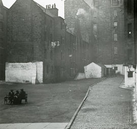 Open area surrounded by tenements with whitewashed ground floor facades