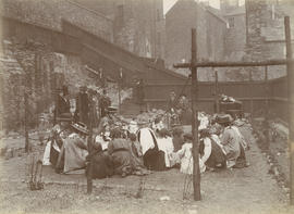 Photograph of group of children and women playing in a garden, probably not West Port Garden, Edinburgh