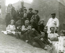 Group of adults, including a policeman, and some children resting on a grass embankment