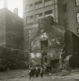 View of backcourt with a partly demolished two storey building in front of a taller brick buildin...