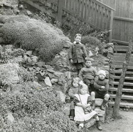 Group of children seated on rocks in backcourt garden
