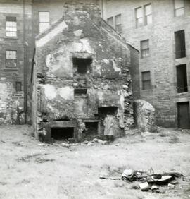 Backcourt scene with a man in court, partly demolished two storey building in background [McConna...