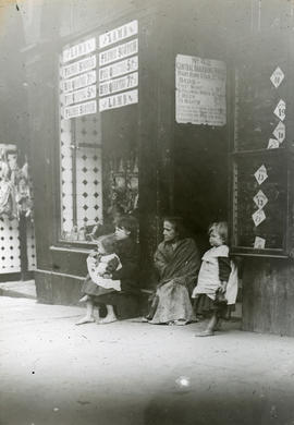 Three children and an elderly woman sitting outside a butcher's shop