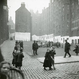 Open area surrounded by tenements with whitewashed ground floor facades, with various people and children in the foreground