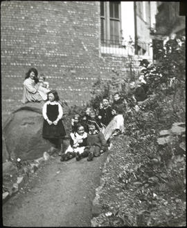 Group of children seated in backcourt garden