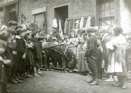 Street scene with a group of children around a trader and his pony