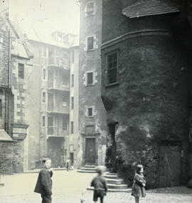 Backcourt with children and round stairwell in foreground